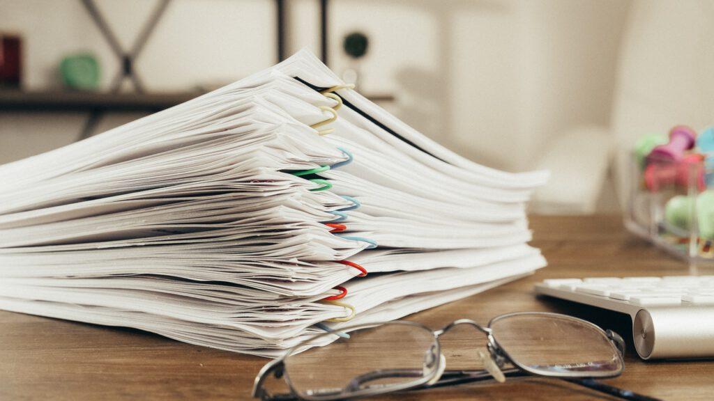 Stapel voll Papier rund um die Themen Lohnsteuer und Umsatzsteuer